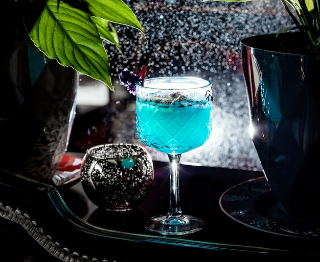Verre en cristal avec cocktail bleu garni de pétales de rose
