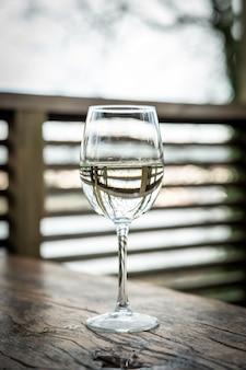 Verre en cristal avec du vin blanc placé sur une balustrade en bois sur la terrasse de la maison située dans la nature