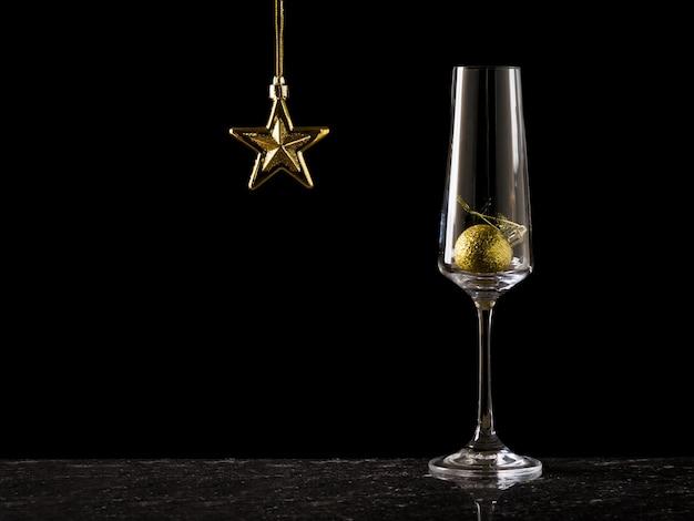Verre de cristal élégant et décorations de noël or sur surface noire