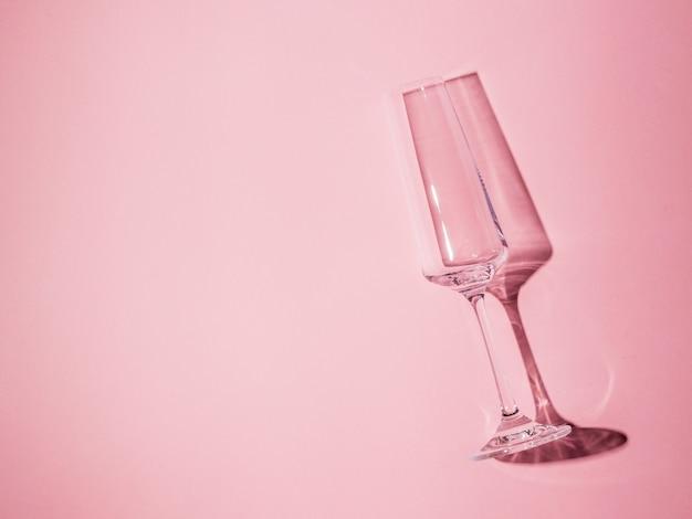 Verre en cristal vide avec tige en lumière vive sur fond rose. verrerie à la lumière dure.