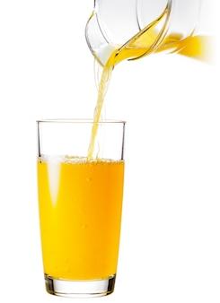 Verre avec une cruche de jus d'orange versé d'une cruche