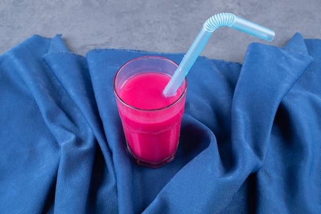 Verre avec un délicieux smoothie aux fraises sur fond bleu.