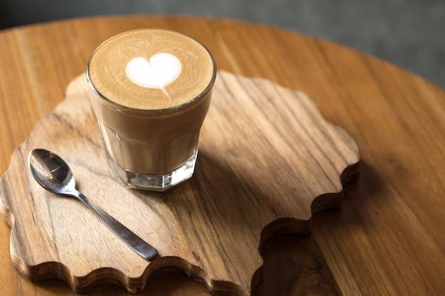 Verre de ce dernier savoureux avec amour art sur la table en bois et le bureau texturé.