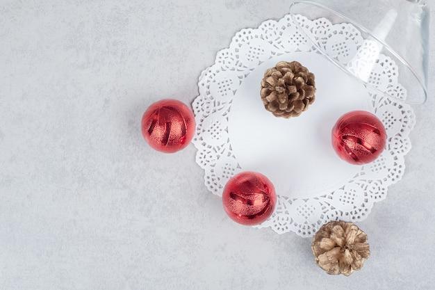 Un verre de deux pommes de pin et trois boules de noël rouges sur fond blanc. photo de haute qualité