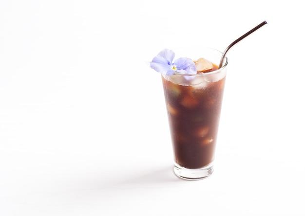 Un verre avec du café froid et des glaçons se dresse sur un fond blanc.