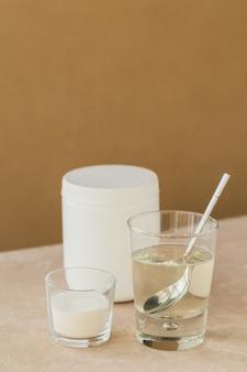 Verre avec du collagène dissous dans de l'eau et de la poudre de protéine de collagène sur une table beige clair. concept de mode de vie sain.
