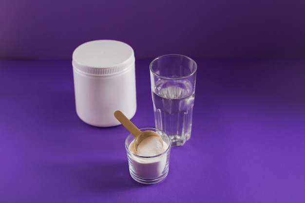 Verre avec du collagène dissous dans de l'eau et de la poudre de protéine de collagène sur table violette