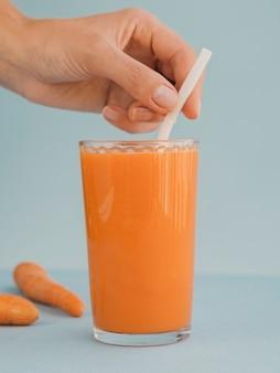 Verre avec du jus de carotte frais et biologique