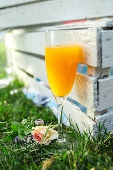 Verre avec du jus d'orange sur l'herbe verte à côté de la boîte en bois.