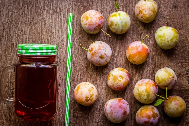 Verre avec du jus de prune frais sur fond de bois vintage