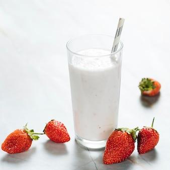 Verre avec du lait et des fraises sur fond uni