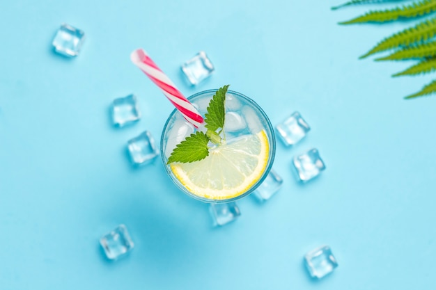 Verre d'eau ou de boisson avec de la glace, du citron et de la menthe sur une surface bleue avec des feuilles de palmier et de fougère. glaçon. concept d'été chaud, alcool, boisson rafraîchissante, étancher la soif, bar. mise à plat, vue de dessus