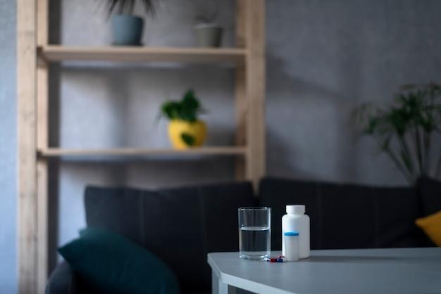 Verre d'eau et bouteille de pilules sur table dans un salon vide. concept de santé, traitement.