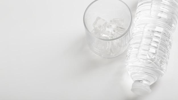 Verre d'eau et bouteille en plastique espace copie blanche