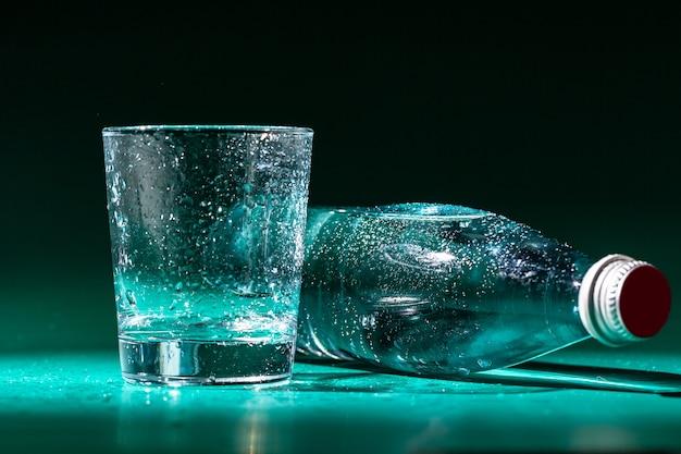 Verre d'eau avec une bouteille sur table