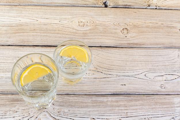 Verre d'eau et de citron sur une table en bois
