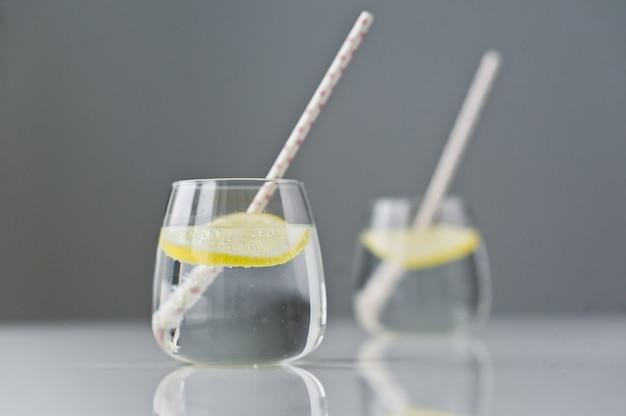 Verre d'eau claire au citron et à la paille.