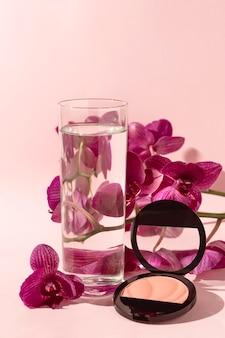 Verre avec de l'eau à côté de fleurs