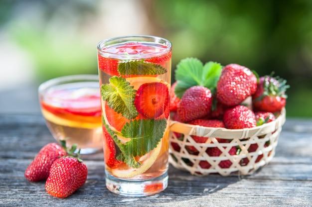 Verre d'eau détox. fraise, citron et menthe avec de l'eau fraîche et propre, toile de fond d'un jardin verdoyant.