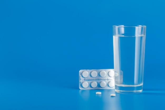 Verre avec de l'eau et diverses pilules isolés sur fond bleu avec espace copie