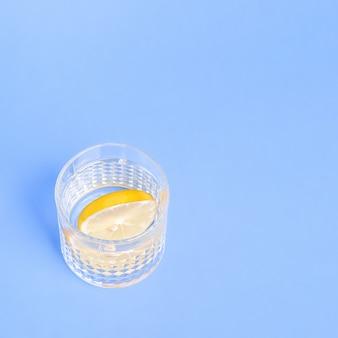 Verre avec de l'eau et du citron sur fond bleu