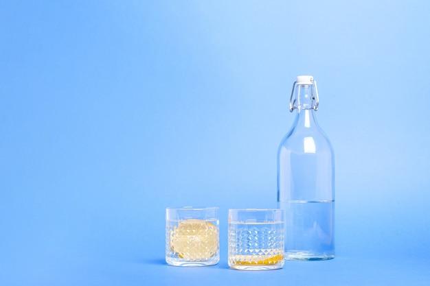 Verre avec de l'eau et du citron près de la bouteille sur une surface bleue