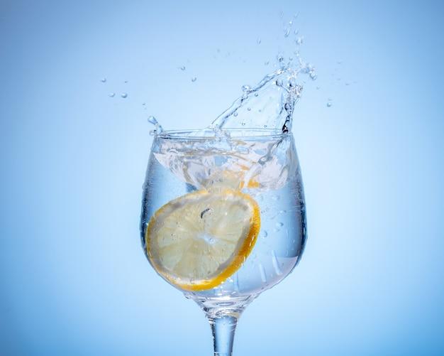 Verre d'eau avec du citron tombé et éclabousser sur fond dégradé bleu clair.