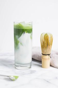 Verre d'eau avec des feuilles de légumes sur une surface blanche