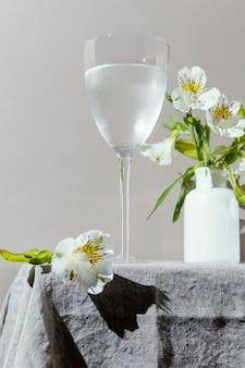 Verre d'eau et fleurs sur table