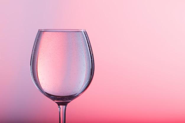 Verre d'eau sur fond rose