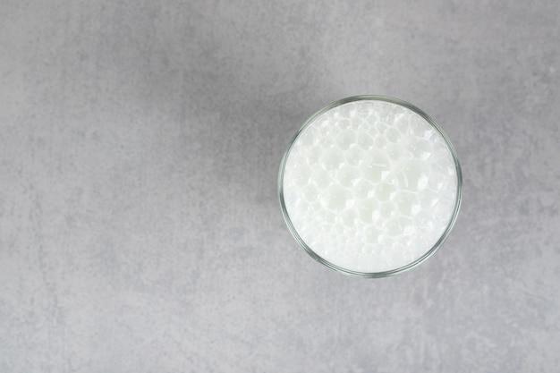 Un verre d'eau froide pure avec des bulles sur une surface grise