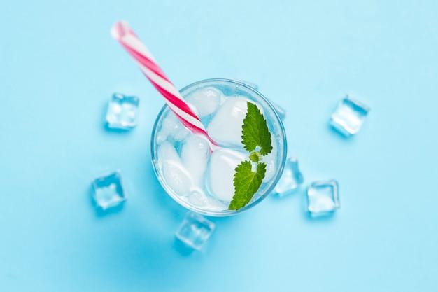 Verre d'eau froide et rafraîchissante avec de la glace et de la menthe sur fond bleu. glaçon. concept d'été chaud, alcool, boisson rafraîchissante, étancher la soif, bar. mise à plat, vue de dessus