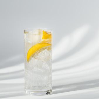Verre d'eau gazeuse minérale propre avec de la glace et du citron sur un fond blanc avec du soleil. lumière avec des ombres dures et l'éblouissement du verre. petit-déjeuner, boisson fraîche du matin