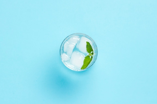 Verre d'eau avec de la glace et de la menthe sur fond bleu. concept d'été chaud, alcool, boisson rafraîchissante, étancher la soif, bar. mise à plat, vue de dessus