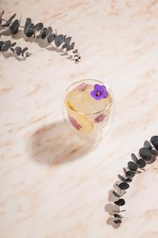 Un verre d'eau glacée décoré de fleurs avec des branches d'eucalyptus autour d'une table en marbre.