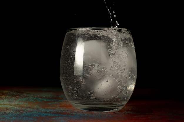 Verre d'eau glacée rempli d'eau gazeuse froide sur un fond sombre et une surface rustique.