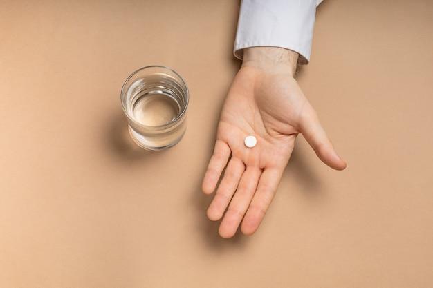 Verre d'eau et médicament à la main