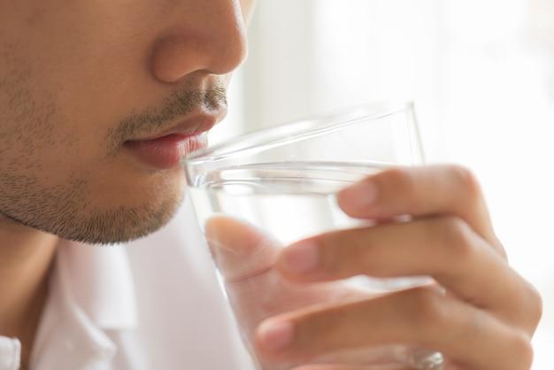 Un verre d'eau minérale propre dans les mains de l'homme. concept de boisson saine.
