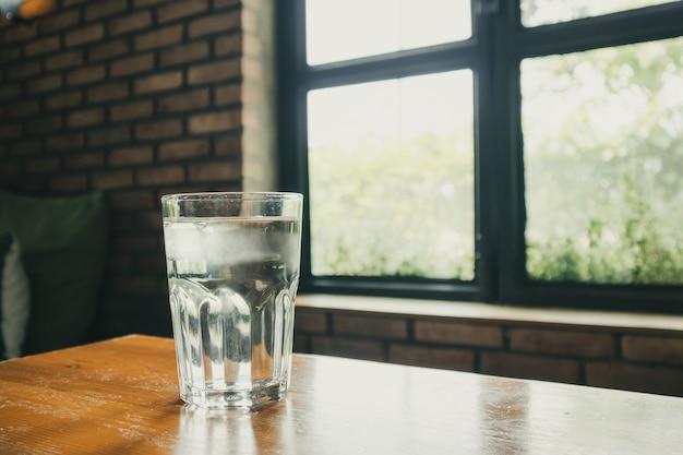 Verre d'eau minérale sur table en bois au restaurant