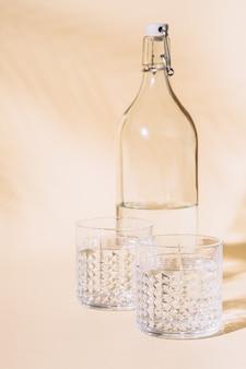 Verre d'eau sur un mur pastel près de la bouteille