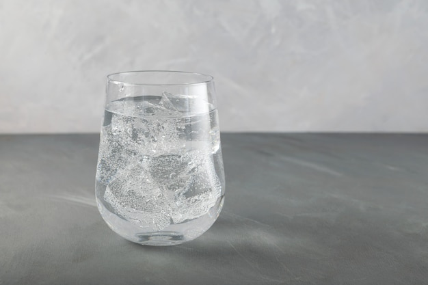 Verre d'eau pétillante pure avec de la glace, gros plan