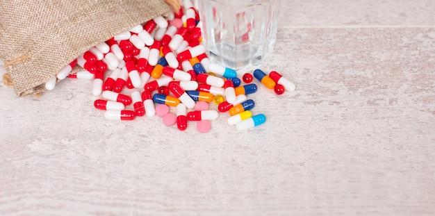 Verre d'eau et pilules colorées sur table