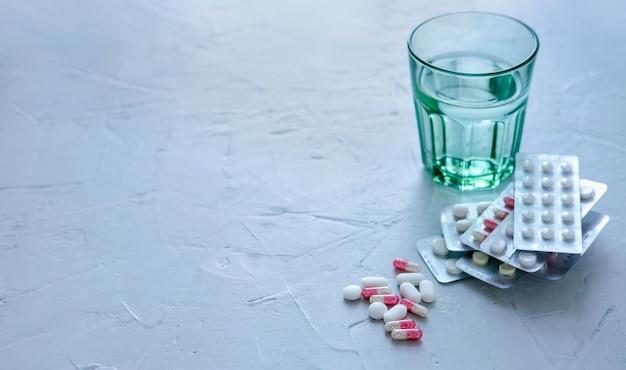 Verre d'eau avec des pilules et des comprimés sur la surface grise.