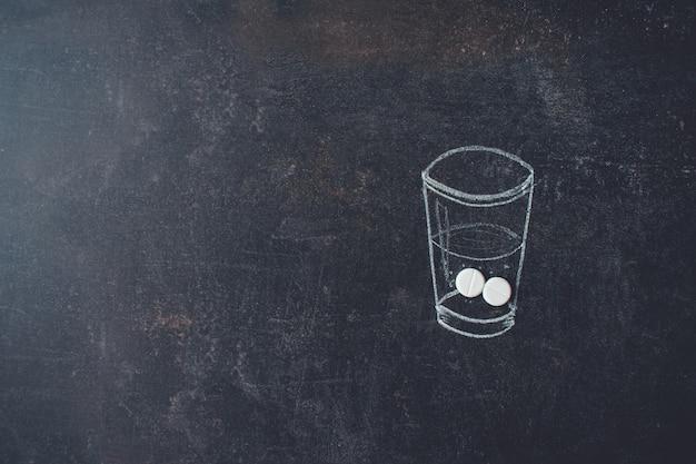 Verre d'eau et pilules dessinés à la craie