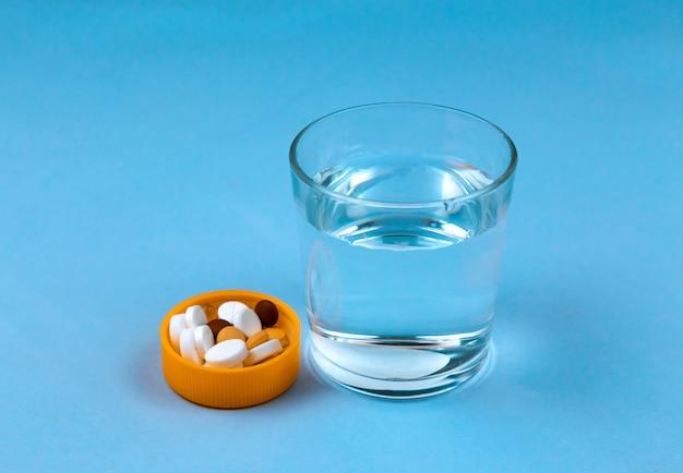 Verre d'eau et des pilules sur fond bleu