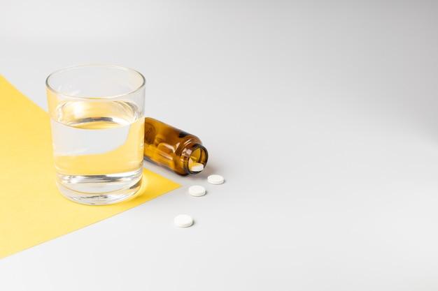 Verre d'eau et pilules d'un pot sur fond blanc et jaune