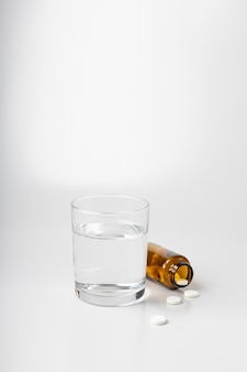 Verre d'eau et pilules d'un pot sur fond blanc