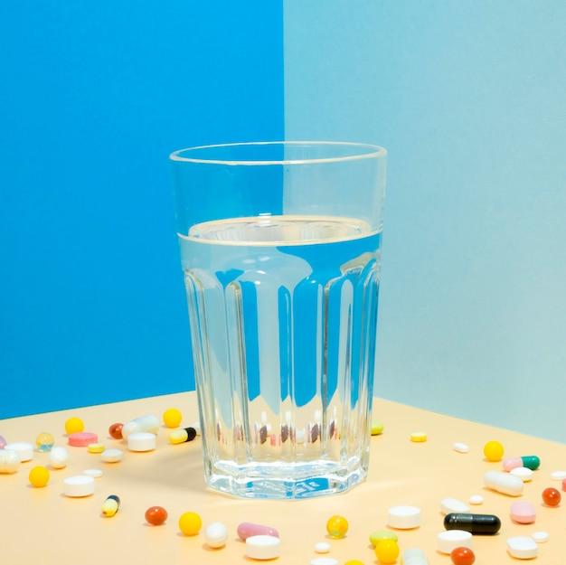 Verre d'eau avec des pilules qui l'entourent