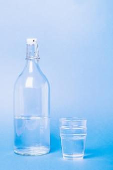 Verre avec de l'eau près de la bouteille sur bleu