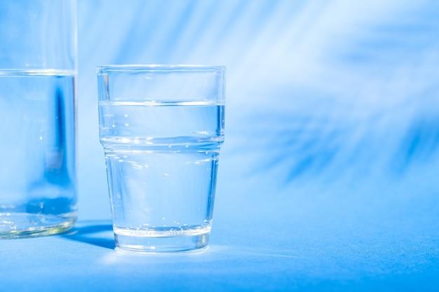 Verre avec de l'eau près de la bouteille sur fond bleu